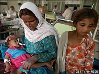Mujer con sus hijos en hospital de Pakistán