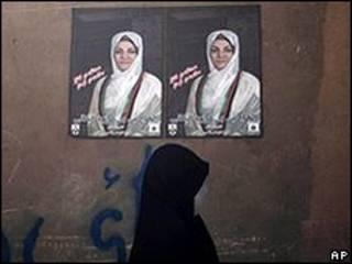 Mulher passa em frente a cartaz de campanha de Fauzia Galani, em Herat