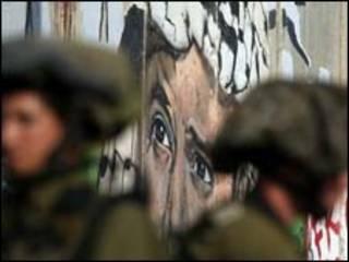 Soldados israelenses em frente a imagem de Yasser Arafat