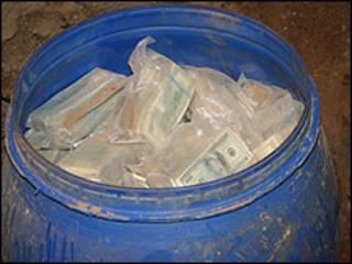 Barril lleno con dinero mostrado por la policía salvadoreña a la prensa.