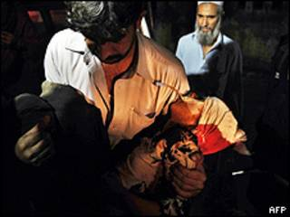 Homem carrega vítima de ataque em Kohat, Paquistão (AFP/Getty)
