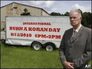 """Пастор Джонс на фоне своей церкви и надписи: """"Международный день сожжения Корана"""""""