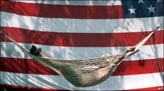 Человек отдыхает в гамаке на фоне американского флага