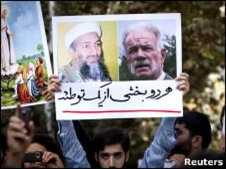 """متظظاهر رفع لافتة تحمل صورة للقس الأمريكي ولزعيم القاعدة كتب تحتها: """"وجهان لمؤامرة واحدة"""""""