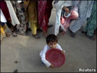 Menino paquistanês espera distribuição de alimentos em campo de refugiados