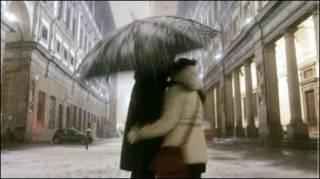 یک زوج در برف یکدیگر را می بوسند