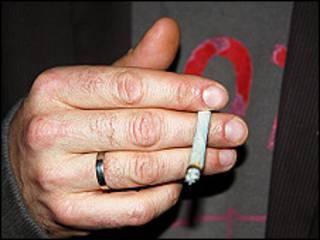 Un hombre sostiene un cigarro de marihuana