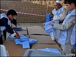 Tres hombres cuentan las papeletas de votación
