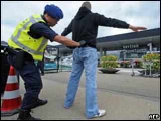 Полицейский досматривает мужчину в аэропорту Схипхол