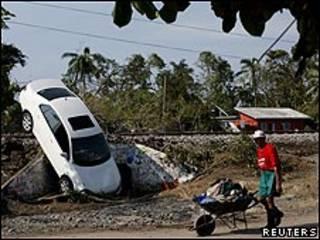Un vecino de Samoral, cerca de Veracruz, empuja un carro con sus pertenencias.