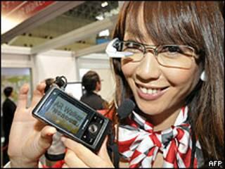 Una joven muestra los lentes y su teléfono celular con la aplicación para el AR Walker