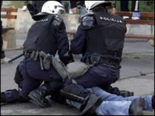 Manifestante é contido por policial em Belgrado