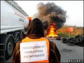 Рабочий французской нефтяной фирмы Total около баррикад, прегрждающих путь на НПЗ