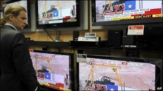 Cliente de loja de eletrodomésticos em frente a TVs ligadas no caso do Chile