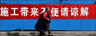 Una mujer camina frente a un letrero en Pekín