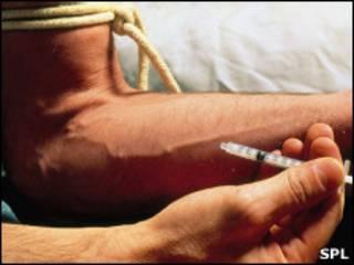 Наркоман впрыскивает героин шприцем в вену