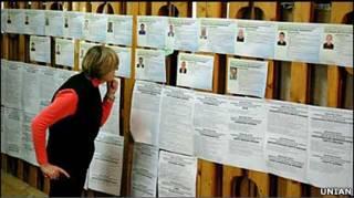 жінка дивиться на списки кандидатів у депутати