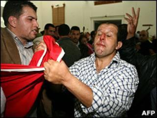 ناشط صحراوي يحاول سحب العلم المغربي من مواطن مغربي خارج محكمة في الدار البيضاء حيث يحاكم أحد أعضاء جبهة بوليساريو