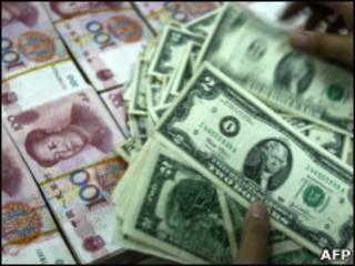 Funcionário de banco na China conta notas de dólar e iuan