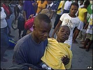 Homem carrega criança doente em Porto Príncipe