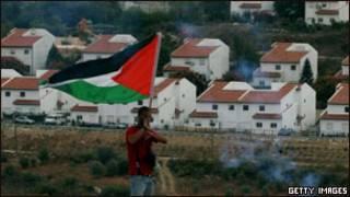 محتج يحمل العلم الفلسطيني يقف قبالة مستوطنة اسرائيلية