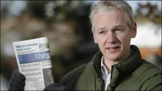 جوليان اسانج يحمل صحيفة الجارديان