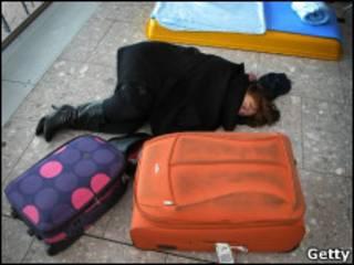 Mulher dorme no chão do aeroporto de Heathrow