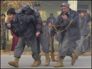 شرطيان افغانيان ينقلان زميلاً جريحاً