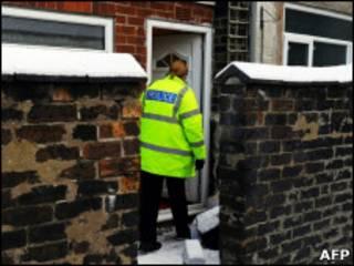 Policial em frente a casa de Stoke-on-Trent onde suspeitos foram presos