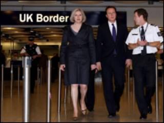 Министр внутренних дел Тереза Мэй и премьер-министр Дэвид Кэмерон в лондонском аэропорту Хитроу