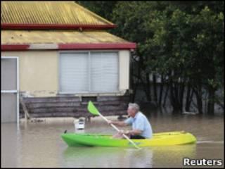 Человек в лодке на затопленной наводнением улице города Бундаберг, штат Квинсленд, Австралия