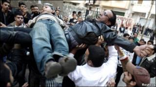متظاهران يرسمان الصليب بجسديهما