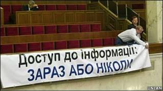 Депутат БЮТ Андрій Шевченко вішає плакат під час засідання Верховної Ради 2 листопада 2010 р.