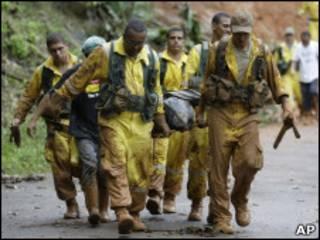 Equipe de resgate retira corpo de vítima de deslizamento