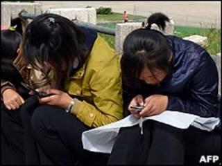 朝鮮平壤街頭兩名少女蹲坐路旁使用手機(22/9/2010)