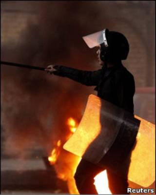 Policial em meio a confronto com manifestantes no Egito