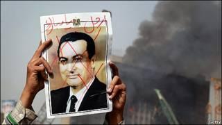 Manifestante con una foto tachada de Mubarak
