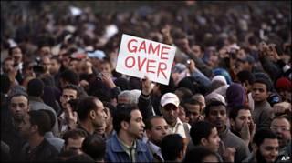 埃及開羅解放廣場上一名示威者舉起「遊戲結束」的抗議標語(29/1/2011)
