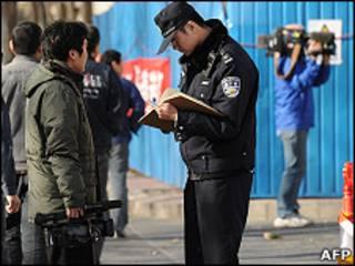 北京警察在被囚諾貝爾和平獎得主劉曉波的寓所外查核記者證件(10/12/2010)