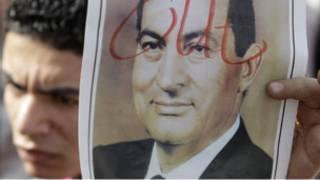 """متظاهر وصورة لمبارك وقد كُتبت عليها كلمة """"اخرج"""" بالإنكليزية"""