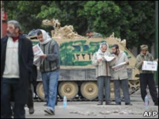 Manifestantes leem jornal na Praça Tahrir