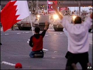 Manifestantes se ajoelham em frente a tanques do Exército, no centro de Manama, Bahrein (AP)