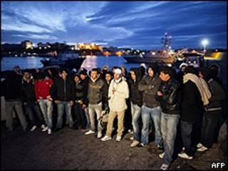 Imigrantes aguardam transporte para centro de triagem em Lampedusa (AFP)