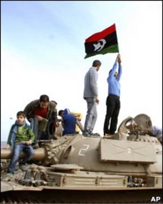 Manifestantes na cidade líbia de Benghazi seguram bandeira da época pré-Khadafi