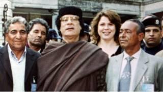 القذافي وخلفه احدى ممرضاته