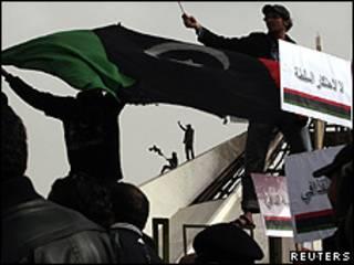 Manifestantes com uma bandeira antiga da Líbia em um prédio de Benghazi (Reuters)