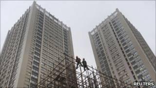 Двое китайских рабочих на фоне стройки