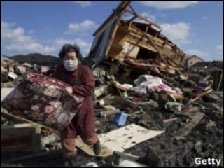 Sobrevivente do tsunami recolhe pertences de casa destruída