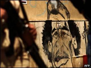 Rebelde ao lado de caricatura de Khadafi em Benghazi