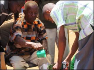 Curandeiro tradicional serve sua célebre poção a um de seus inúmeros fiéis ( David Wambundo - BBC)